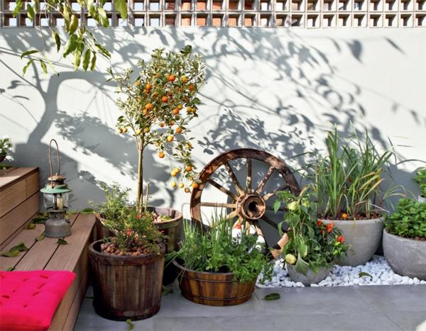 terrassengestaltung modern balkonpflanzen orangenbaum bodenfliesen kieselsteine