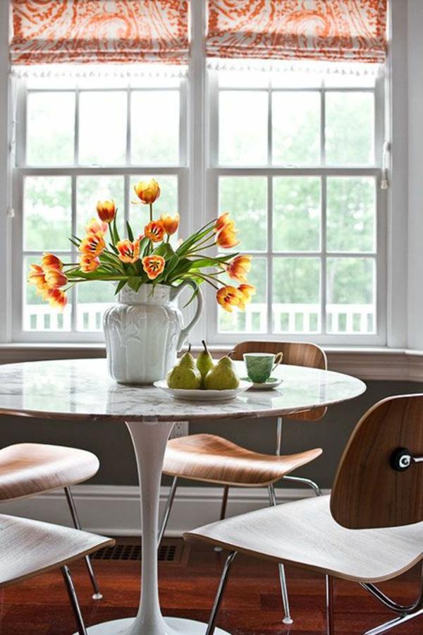 runder esszimmertisch mit stühlen vase mit tulpen