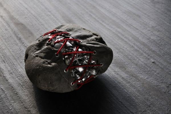 steinskulpturen stein voller metallenen muscheln