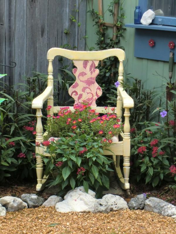 garten dekorieren hölzerner alter stuhl blumen steine