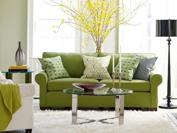 kleines wohnzimmer grünes sofa weißer teppich glastisch