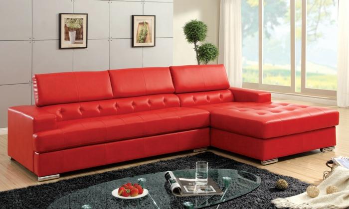 rote sofas wohnzimmer grauer teppich gläserner ovaler couchtisch