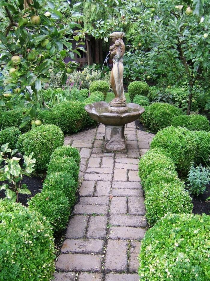 gartenweg aus stein führt zum gartenbrunnen