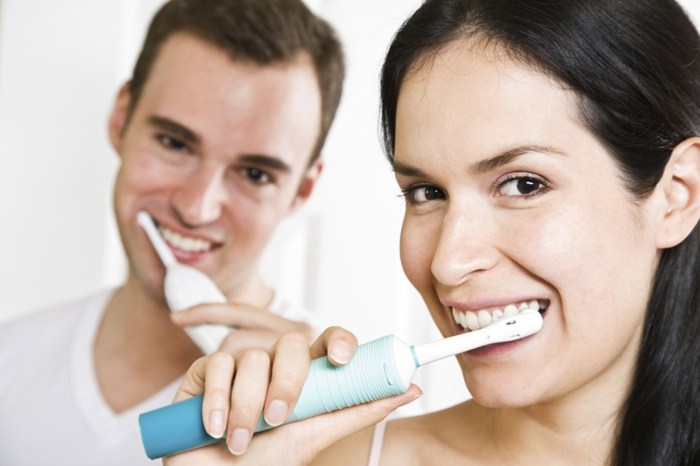 A beautiful interracial couple in the bathroom brushing teeth