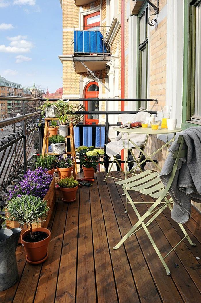 balkongestaltung hellgrüne stühle runder balkontisch blumen