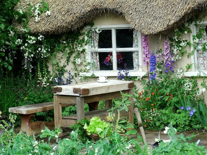 cottage garten blumen grüne pflanzen strohdack bank tisch