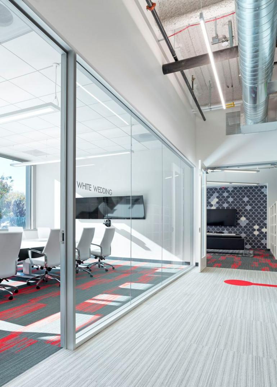 Moderne Büroeinrichtung mit roten Farbakzenten vom Blitz Design Studio