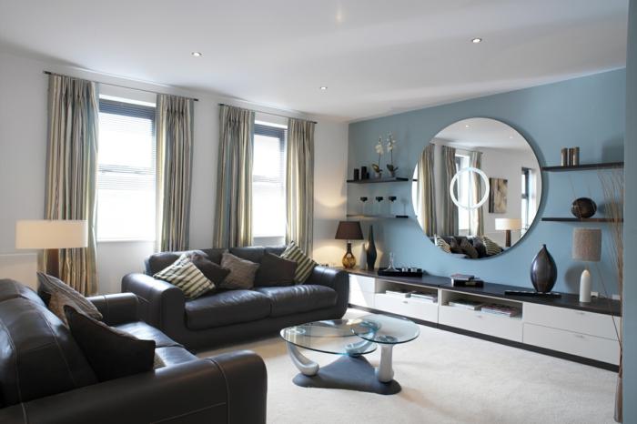 wohnzimmergestaltung blaue akzentwand runder wandspiegel schwarze ledersofas
