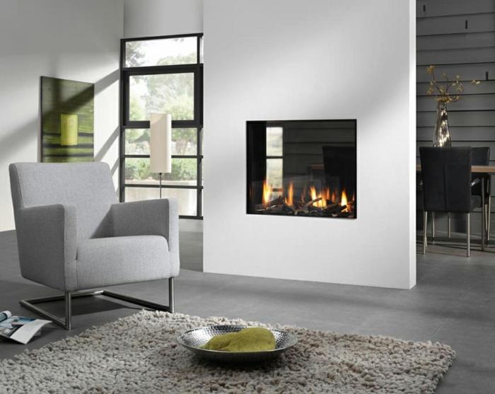 innendesign wohnzimmer kamin teppich weiße wände hellgrauer sessel