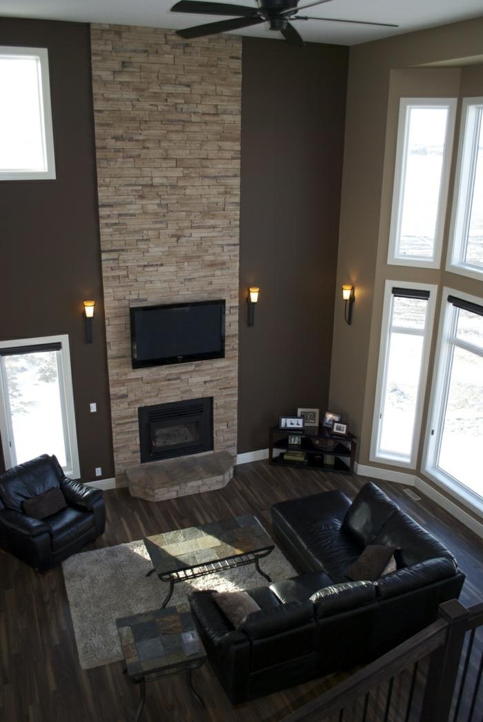 kaminfeuer kamin wanddeko steine wohnzimmer schwarze ledermöbel