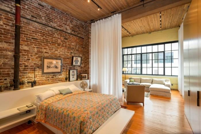 schlafzimmer einrichten ziegelwand und frische bettwäsche in warmen farbtönen