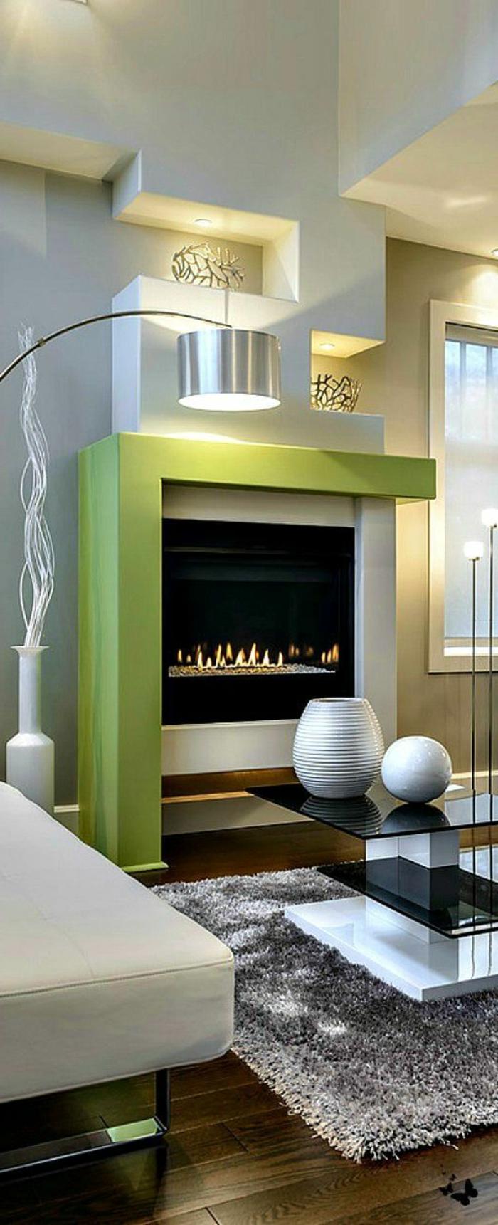 kamin design wohnzimmer einrichten grauer teppich grüne akzente