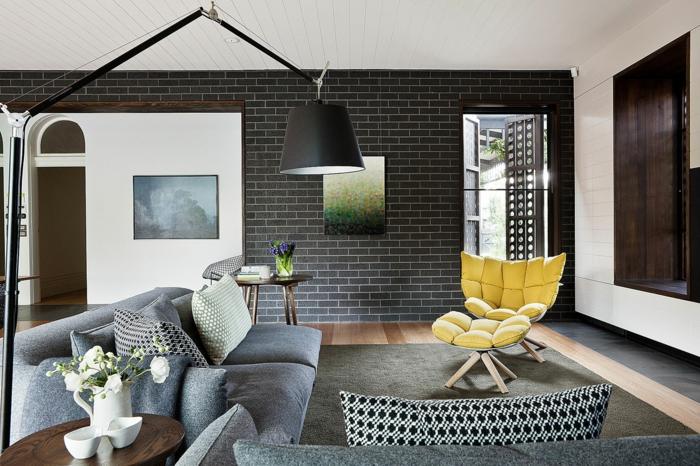 wände gestalten wohnzimmer dunkle wandfliesen gelber sessel graues sofa