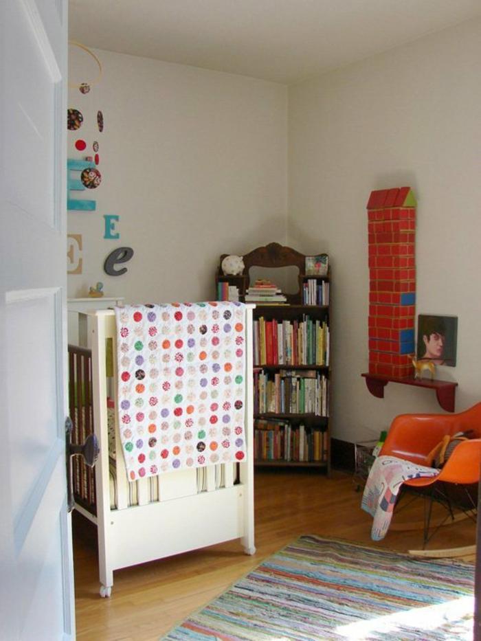 babybetten design weiß farbiger streifenteppich oranger schaukelstuhl offene bücherregale