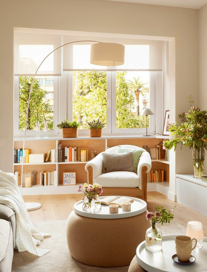 kleines wohnzimmer einrichten runde beistelltische ottomane bücherregale fensterbank bogenlampe