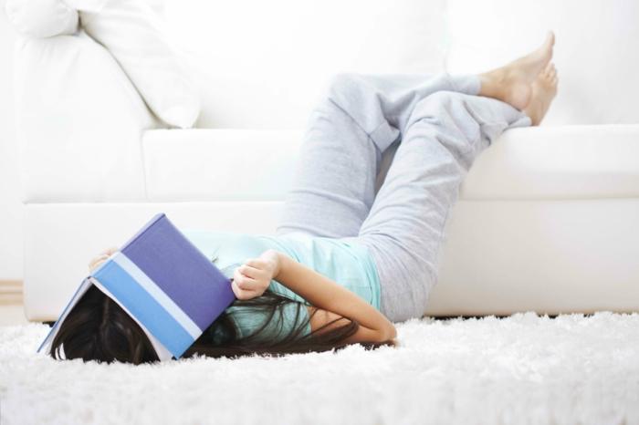 prüfungsangst studentin buch lesend müde wohnzimmer