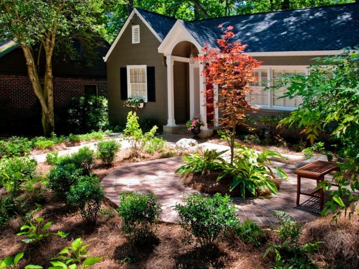 Vorgarten mit Bäumen und Stützmauer aus Naturstein