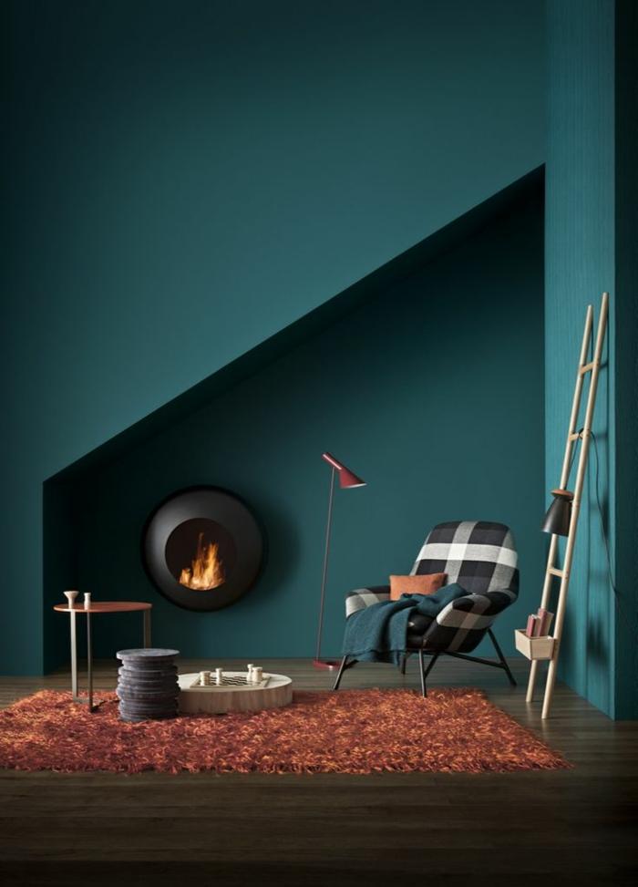 wanfarben ideen dunkelgrüne wandfarbe oranger teppich moderner kamin wohnbereich
