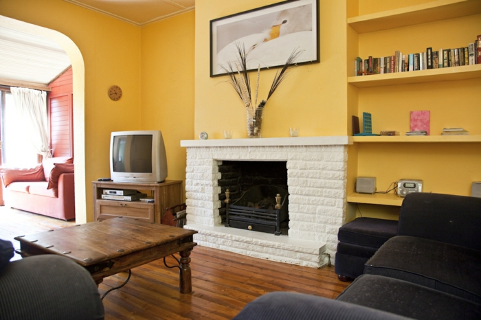 wohnzimmer-streichen-ideen-gelbe-wandfarbe-kamin-schwarz-wohnzimmermöbel.jpg