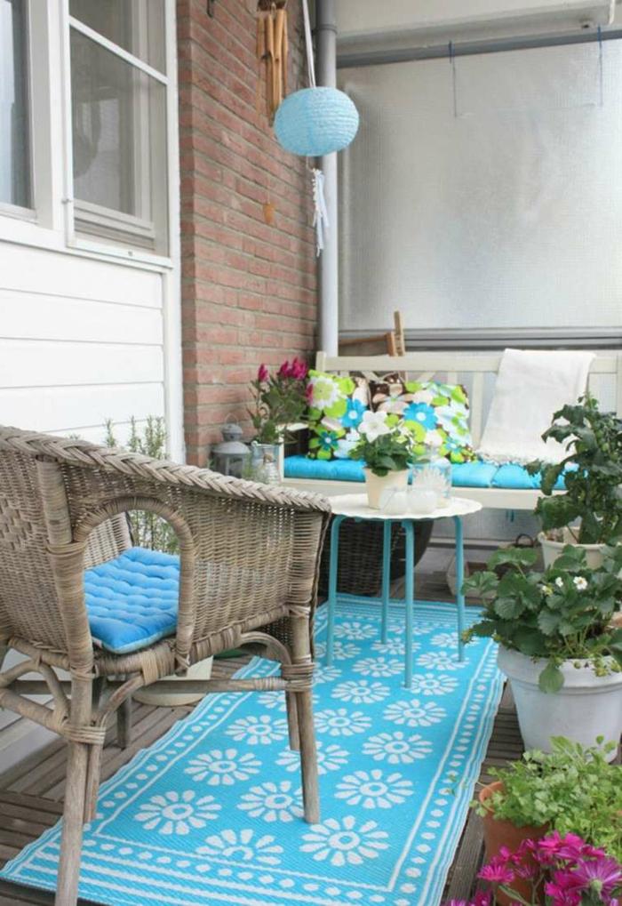 balkon gestalten blauer teppichläufer rattanmöbel blumentöpfe