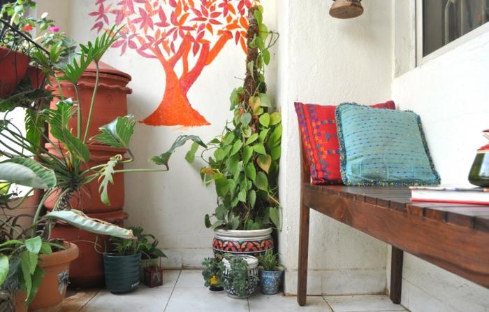 balkon gestalten pflanzen gartenbank bodenfliesen dekokissen