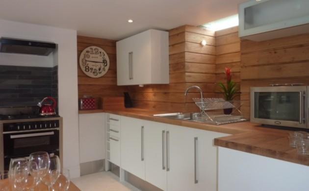 küchendesign-hölzerne-wandpaneele-weiße-küchenschränke