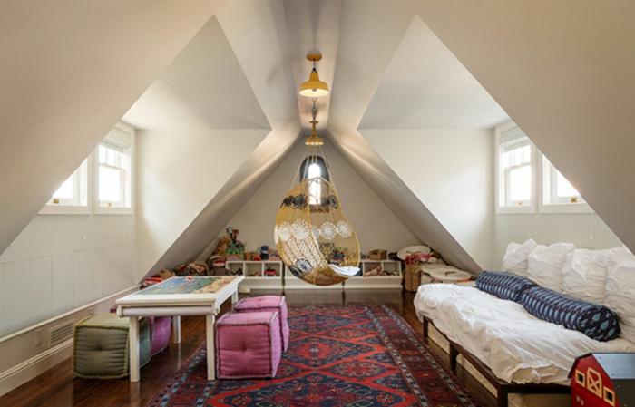 kinderzimmer mit dachschräge schlafsofa hängesitz geflochten weiße poufs tisch spielzeug-teppich