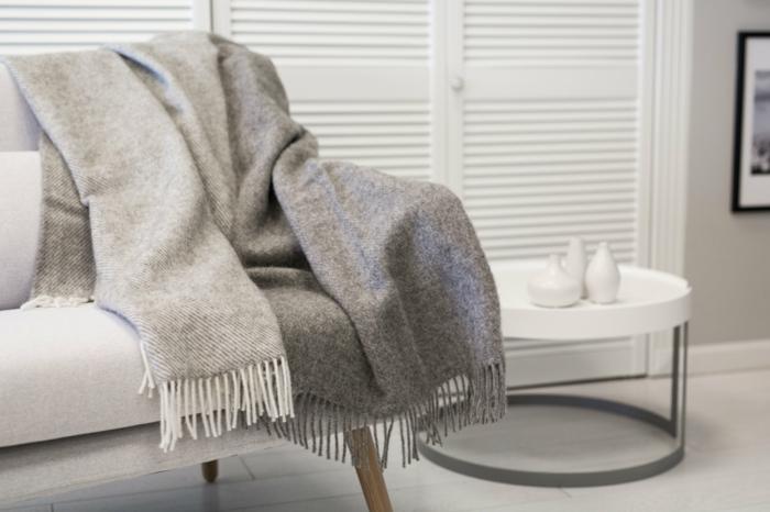 wolldecken wollewarm kuschelig hellgrau hochwertig textilien sofa weiß runder beistelltisch
