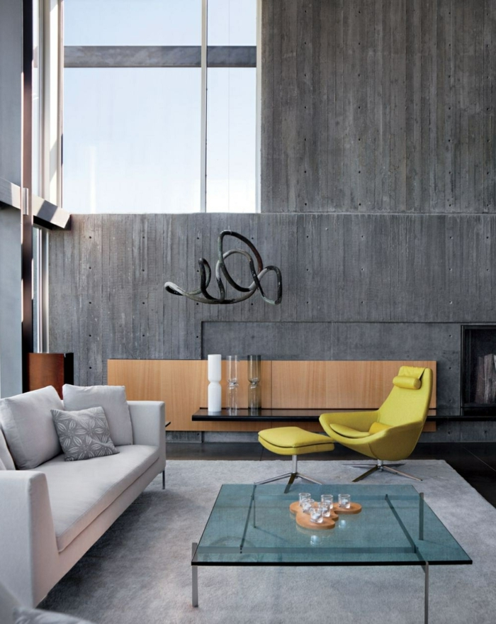 schöne wohnideen wohnzimmer betonwand gläserner couchtisch hellgrauer teppich