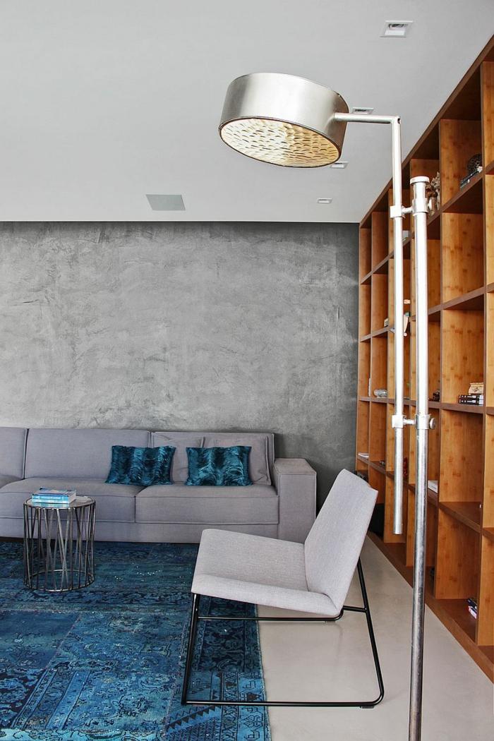 schöne wohnideen wohnzimmer einrichten betonwände blauer teppich regalsystem