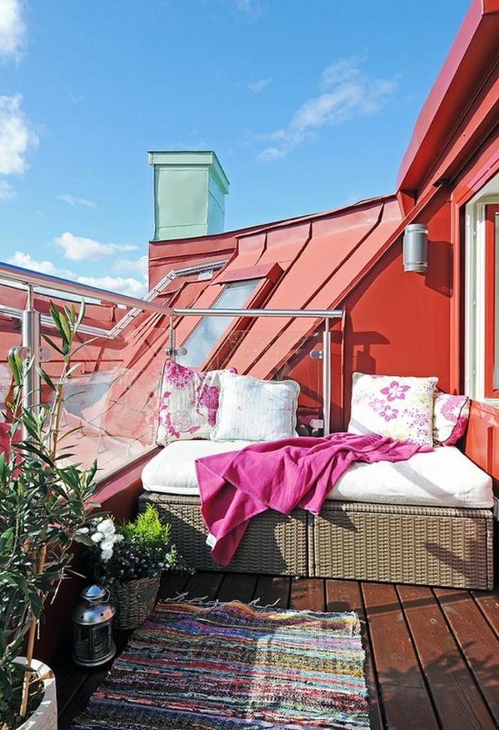 balkoneinrichtung terrassengestaltung bunte kissen rattanmöbel sofa teppichläufer
