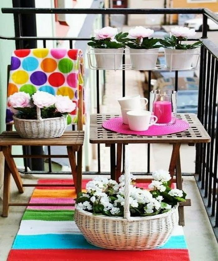 balkonpflanzen frühlingsblumen balkonmöbel holz bunte heimtextilien teppich wolldecke