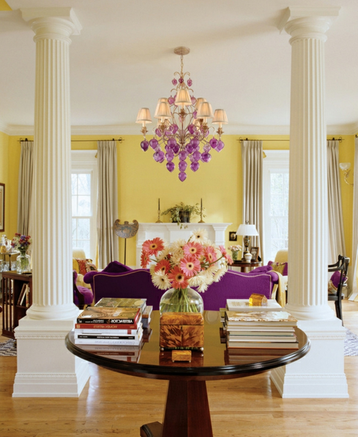farbgestaltung wohnzimmer gestalten gelbe wände weiße säulen violettes sofa