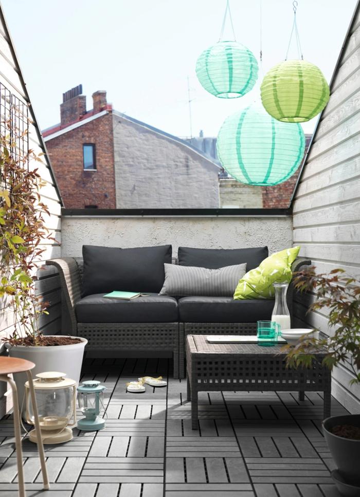 graue balkonmöbel sofa couchtisch holzboden metallene laternen kleiner balkon