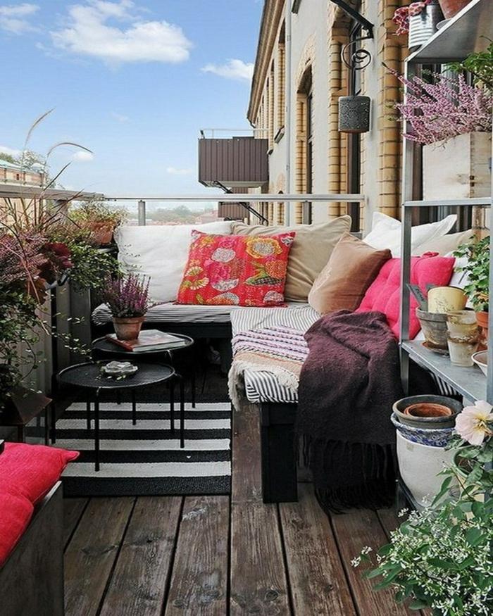 holzdielen-balkonmöbel-bunttextilien kisssen runde beistelltische teppichläufer schwarz weiß streifen balkonpflanzen