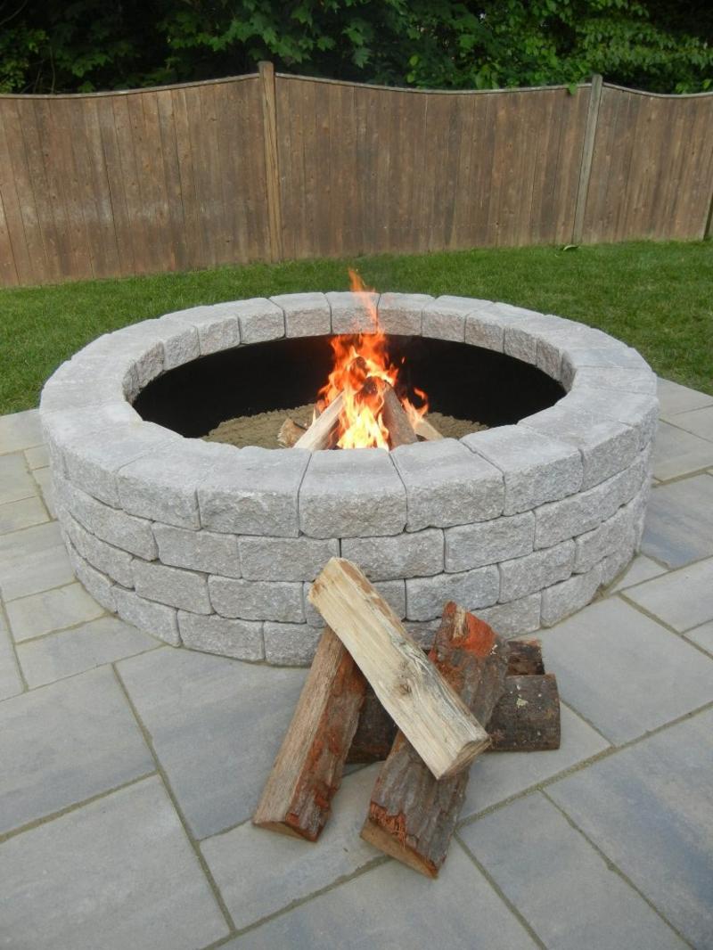 Feuerstelle bauen Steine und Kies Gartengestaltung gemütliche Sommerabende