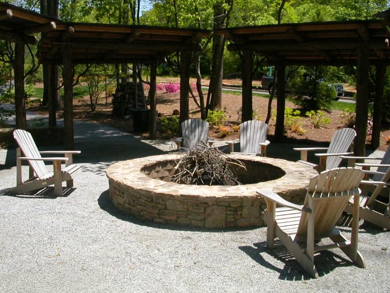 Stein Feuerstelle bauen Gartengestaltung mit Steinen Gartenstühle Holz
