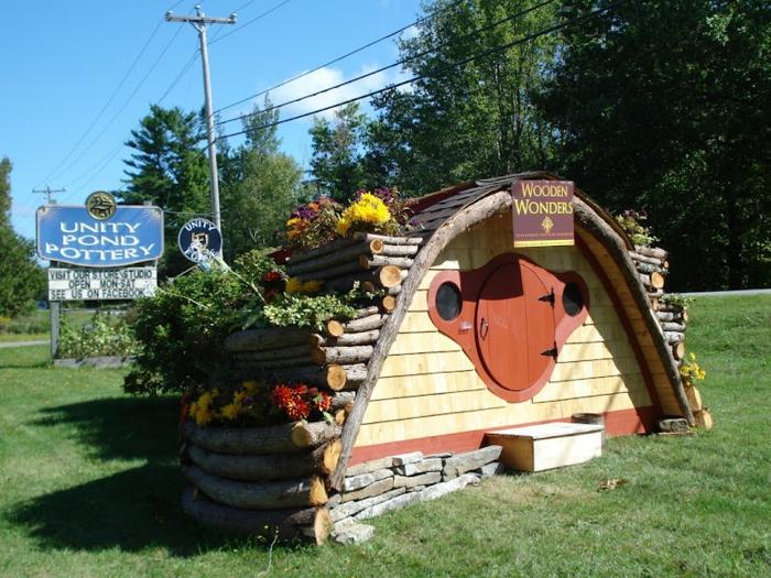 gartenhaus selber bauen holzhaus runde tür baumstämme blumen
