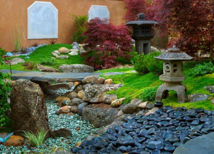 japanischer garten steinerne laternen schwarze flusssteine kieselsteine grünes gras