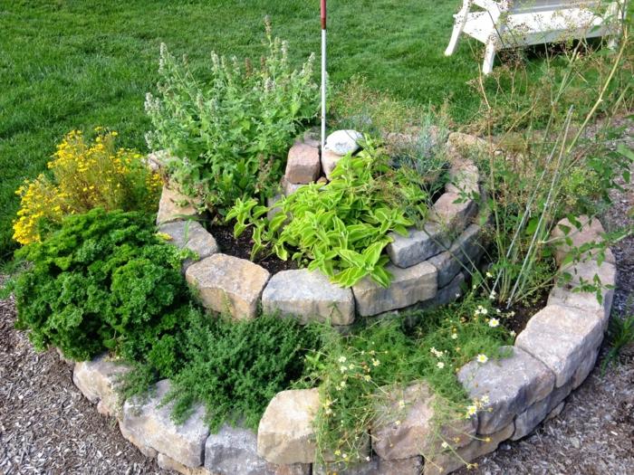 kräuterspirale stein kleine steine voller blüte backsteine heilpflanzen Kräuterspirale bauen