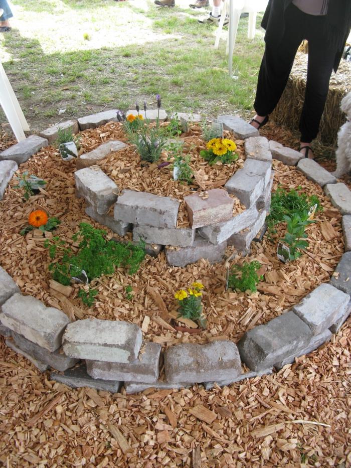 kräuterspirale stein kleine steine voller blüte backsteine Kräuterspirale bauen