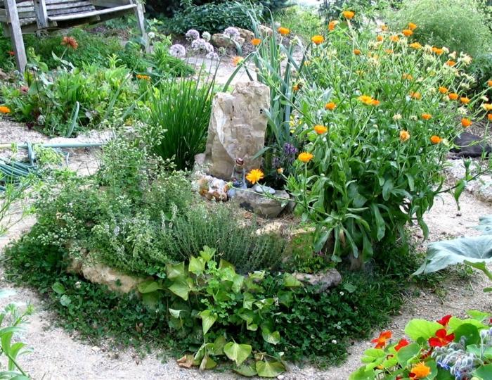 kräuterspirale stein kleine steine voller blüte blumen Kräuterspirale bauen
