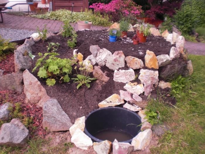 kräuterspirale stein kleine steine volle blüte prächtige nelke Kräuterspirale bauen