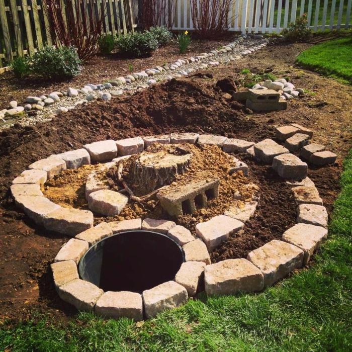 kräuterspirale stein kleine steine voller blüte prächtige steinmauer Kräuterspirale bauen