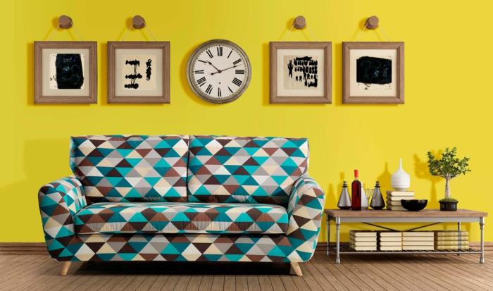 retro gemustertes sofa kommode bücher holzdielen gelbe wandkuns wanduhr portobellodeluxe