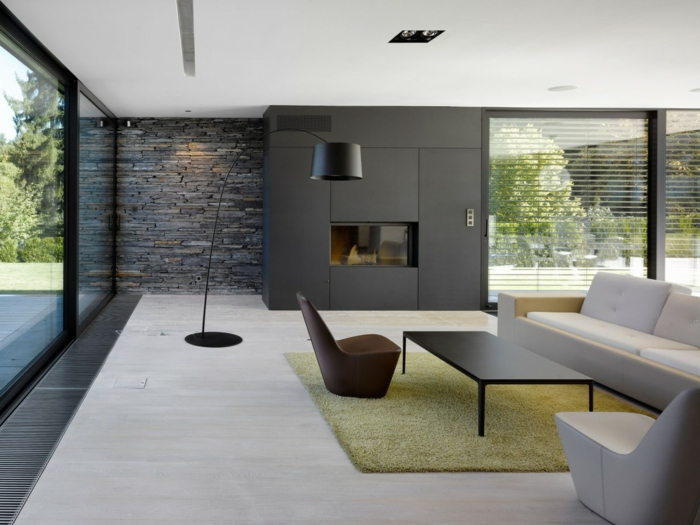 wohnzimmer steinwand akzentwand hellgrüner teppich panoramafenster