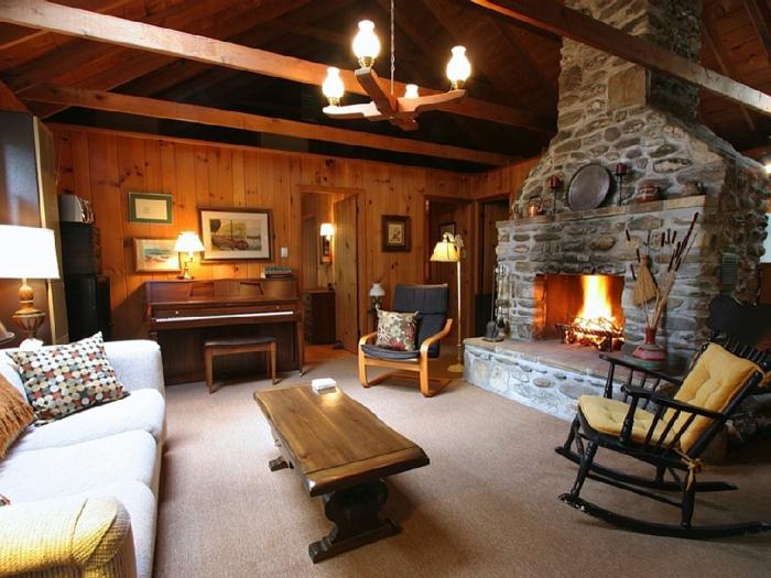 wohnzimmer steinwand kamin rustikaler couchtisch schaukelstuhl ländlicher stil