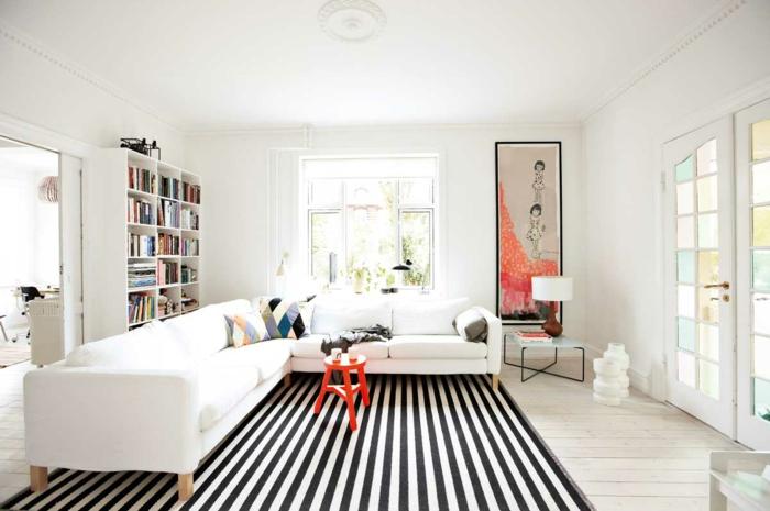 wohnzimmerteppich streifenteppich weiß schwarz weißes ecksofa regalwand roter beistelltisch