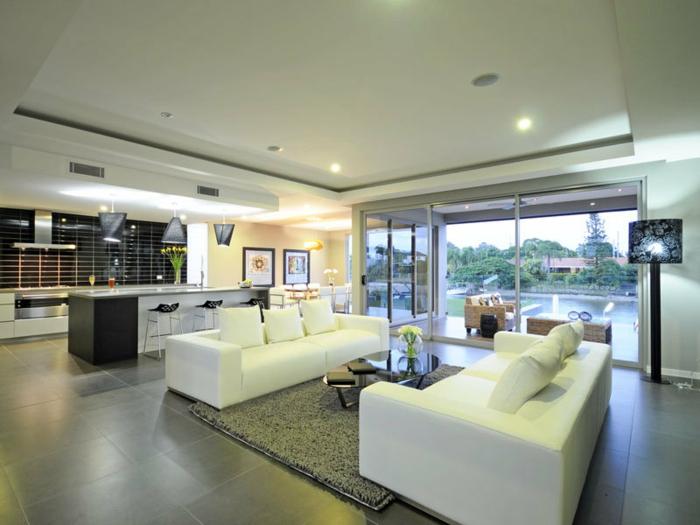 bodenbelag wohnzimmer graue bodenfliesen weiße sofas grauer teppich offener wohnplan