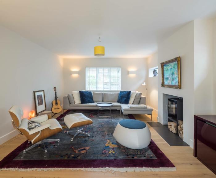 ecksofa hellgraues sofa farbiger teppich relaxsessel weiße wände